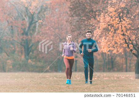 Couple in wonderful fall landscape running for better fitness 70146851