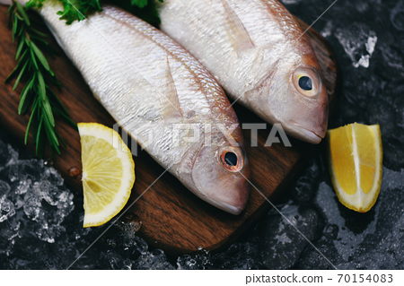 Fresh raw fish with ingredients lemon rosemary and lettuce for making cooked food on ice at market sea bream seafood fish frozen / 70154083