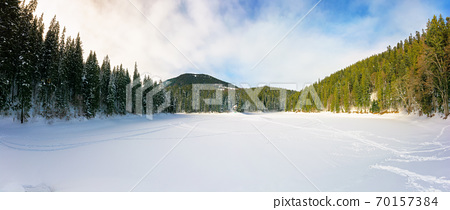 snow covered mountain lake among the forest. green spruce trees on the shore. beautiful sunny weather. clouds on the sky 70157384