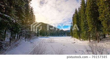 snow covered mountain lake among the forest. green spruce trees on the shore. beautiful sunny weather. clouds on the sky 70157385
