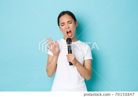 Lifestyle, people and leisure concept. Carefree beautiful asian girl singing sing in microphone with passionate expression, close eyes and gesturing while performing, like karaoke 70158847