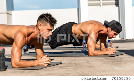 Shirtless muscular sports men doing plank exercise in the open air 70159250