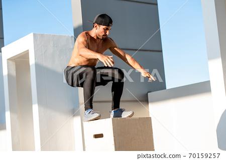 Shirtless athletic man jumping up to plyometric wood box outdoors 70159257