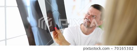 Male patient, together with doctor examines an X-ray. 70165382