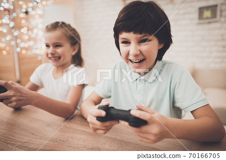 Girl with a joystick sits at a table and plays. 70166705