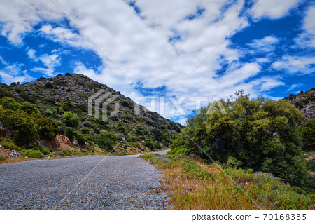 Typical beautiful landscape of Crete island, Greece. Fresh spring foliage, flowers bloom. Gravel drive, blue sky, hills and mountains 70168335