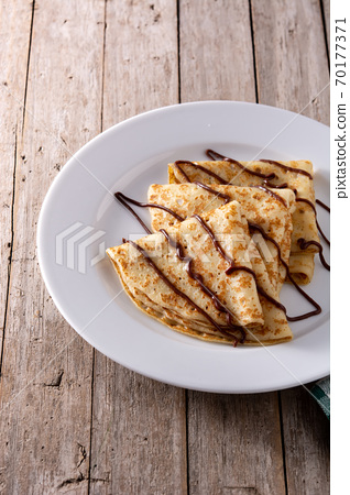 Sweet crepes with chocolate on wooden table 70177371