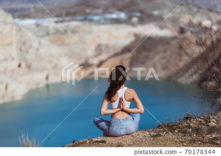 Young pretty woman is practicing yoga at mountain lake early morning. 70178344