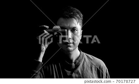 black and white asian man holding retro camera, isolated on black 70178727