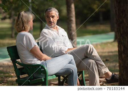 Caucasian middle-aged man smiling looks happy and enjoy conversation with his wife in the warm afternoon sunlight at the park, healthy lifestyle,healthy couple relationship, relax casual communication 70183144
