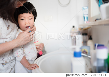 Asian mother helping cute little toddler brushing her teeth, concept healthy happy child, health hygiene, kid oral hygiene, mother should help child brushing teeth, check up from birth to 6 years old. 70183171