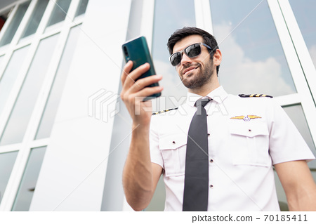 Close up from low angle of aircraft pilot holding and looking at his cell phone and smiling with confidence in the natural sunlight in front of helicopter hangar, aircraft profession. 70185411