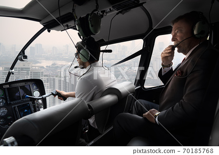 Scene of executive business man on private helicopter while flying over the sky among high pollution in Bangkok city. Concept private flight in rush hour for executive person. 70185768
