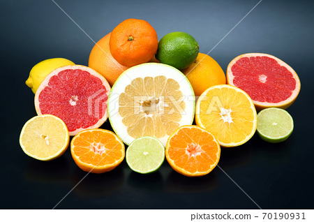 cut pieces of different citrus fruits on dark background 70190931
