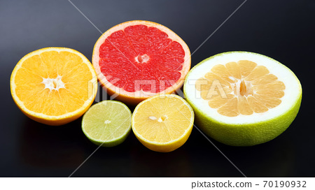 cut pieces of different citrus fruits on dark background 70190932