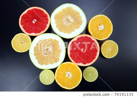 cut pieces of different citrus fruits on dark background 70191135