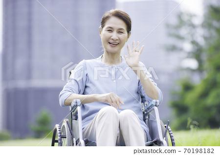 야외에서 휠체어에 앉아 웃는 수석 여성 70198182