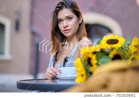 young stylish woman, fashion sunglasses, sitting in cafe, holding drinking cup cappuccino, enjoying, sunflowers, happy stret, city street, europe vacation, romantic dinner, sunny 70203601