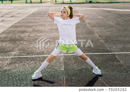 Girl jogging on a sunny summer evening, laying on stadium, physical training, back to school. 70205282