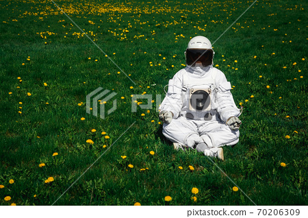 Futuristic astronaut in a helmet sits on a green lawn among flowersin a meditative position. 70206309