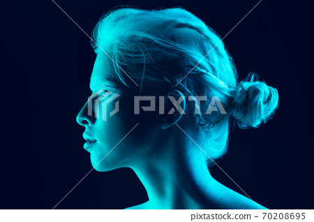 Portrait of beautiful albino girl isolated on dark studio background in neon light 70208695