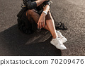 Young woman in stylish white sneakers in a vintage 70209476