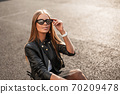 Cheerful pretty young hipster woman in a stylish 70209478
