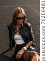 Fashionable young woman in a stylish leather 70209481