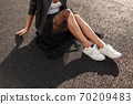 Modern young woman in white stylish shoes in a 70209483