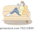 A woman relaxing on the sofa while looking at her cell phone 70213890