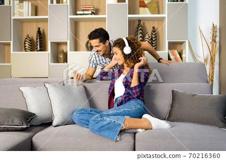 Happy young couple relaxing choosing music 70216360