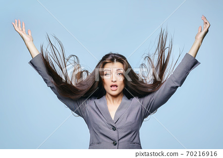 girl with flying hair poses in a Studio on a blue background 70216916