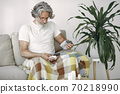Mature man sitting and measuring his blood pressure 70218990