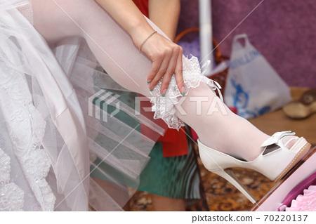 the bride wears a wedding garter 70220137
