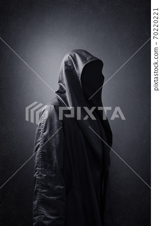 Scary figure in hooded cloak in the dark 70220221
