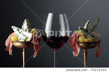 Red wine, blue cheese, prosciutto, grapes, and rosemary on a black background. 70232449