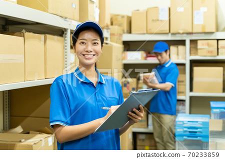 在倉庫里工作的年輕女子 70233859