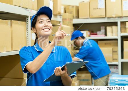 在倉庫里工作的年輕女子 70233868