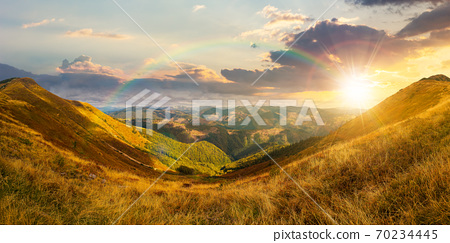 mountain landscape in autumn at sunset. dry colorful grass on the hills. ridge behind the distant valley in evening light. view from the top of a hill. clouds on the sky 70234445