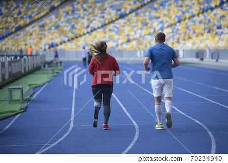 Man and young disabled woman with the prosthetic leg running on the track of the stadium, evening light 70234940