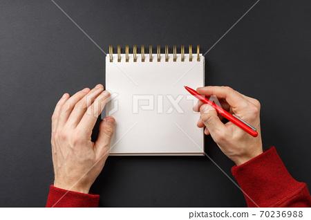 notebook with black pen in hands  70236988