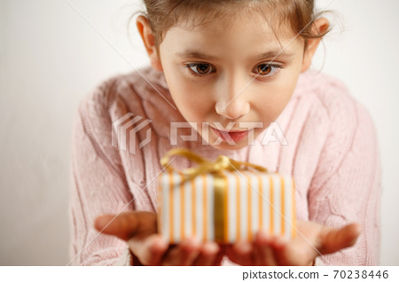 little beautiful girl with gift in her hands 70238446