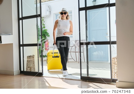 Mature beautiful woman with suitcase in lobby of modern spa resort hotel 70247348