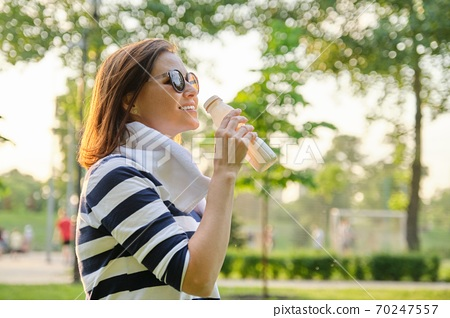 Middle-aged woman drinking milk, dairy product, yogurt from bottle 70247557