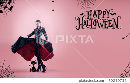 Young brunette woman in hat as a witch, vampire on scary pink background 70250735