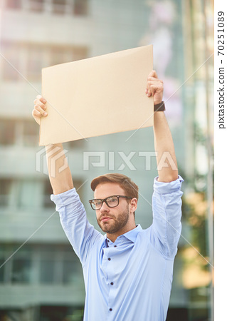 Portrait of a young male activist wearing blue shirt and eyeglasses holding empty sign board while standing outdoors, vertical shot 70251089