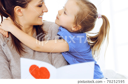 Mother's day concept. Child daughter congratulates mom and gives her postcard with red heart shape. Mum and girl happy smiling and hugging. Family fun and holiday 70252595