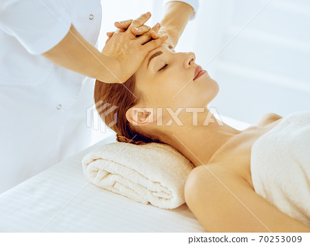 Beautiful woman enjoying facial massage with closed eyes in spa center. Relax treatment concept in medicine 70253009