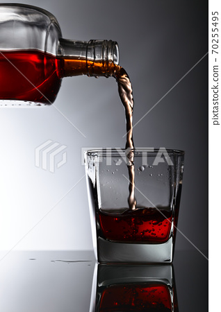 bottle and glass of whiskey on a glass table 70255495