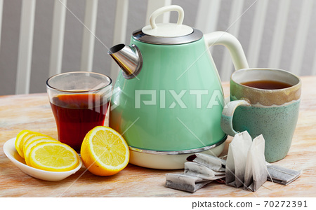 New teapot on table with cup of black tea and sliced lemon 70272391